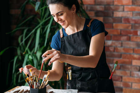 Photo pour Artist workplace. Studio atmosphere. Artwork in process. Smiling young woman in apron choosing paintbrush. - image libre de droit