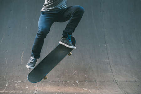 Photo for Skateboarder in action. Extreme sports lifestyle. Hipster performing ollie trick. Cropped shot. Copy space. - Royalty Free Image