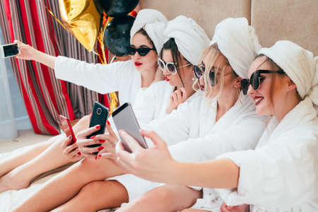 Photo pour Selfie time. Bathrobe girls taking mobile photography. Fun and relaxation habit. Sunglasses and towel turbans on. - image libre de droit