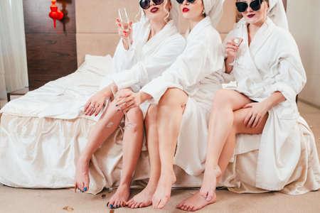 Foto de Women relaxation time. Arrogant females with champagne. Sunglasses, bathrobes and turbans on. Bare legs beauty. - Imagen libre de derechos
