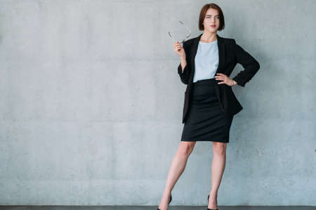 Photo pour Successful business lady. Leadership. Young attractive female with glasses. Copy space on grey background. - image libre de droit