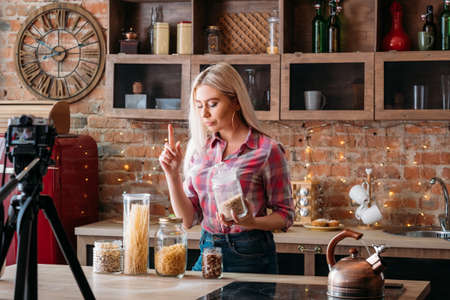 Photo for Food blogger. Female lifestyle. Culinary podcast shooting. Young woman with raised index finger. Jars of pasta, cereals and nuts around. - Royalty Free Image