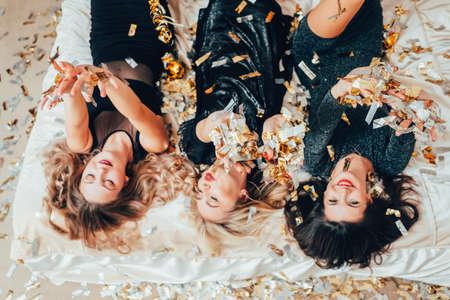 Foto de Theme party. Chill out. Group of women in black relaxing on bed under confetti rain. BFF female gathering excitement. - Imagen libre de derechos