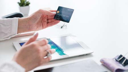 Photo pour Online banking. Credit card payment. Tablet on desk. Plastic money in hand. Woman making transaction. E-payment. - image libre de droit