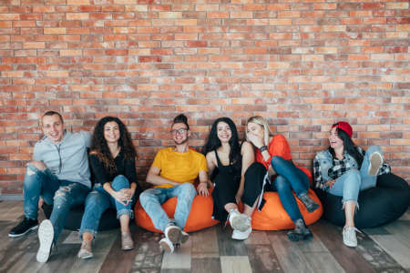 Photo for Millennials chilling out in leisure zone after successful hard working day. Young people sitting in cushion chair, laughing. - Royalty Free Image