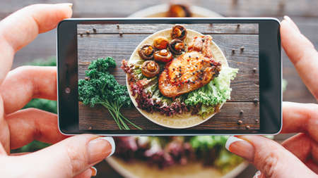 Photo pour Culinary blog. Home cooking hobby. Food recipe. Closeup of female hands taking picture of roasted meat with grilled mushrooms. - image libre de droit