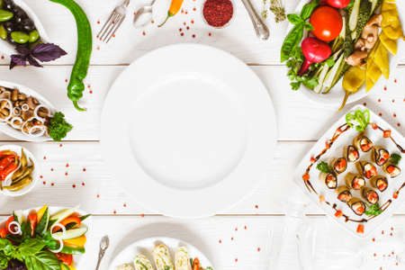 Photo for Food assortment top view. Empty white plate flat lay surrounded by dishes on the table. Buffet catering and restaurant cooking concept. - Royalty Free Image