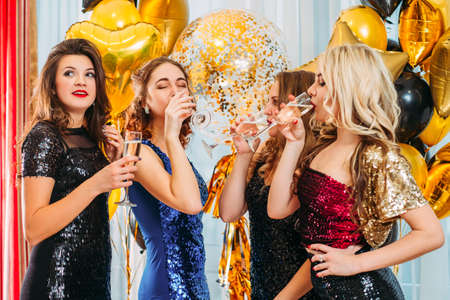 Foto de Fancy corporate party. Girls celebrating, drinking toast to company success in modern office decorated with golden balloons. - Imagen libre de derechos
