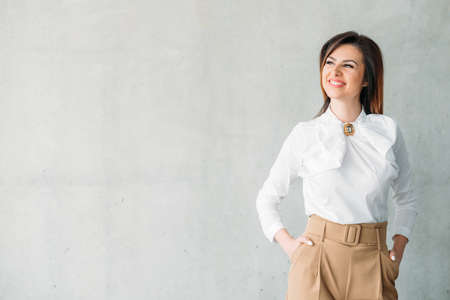 Photo pour Smiling business lady hands in pockets. Beautiful successful female looking into distance. Prosperity contentment delight. - image libre de droit