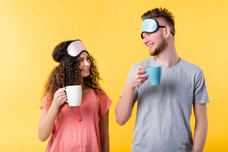 Photo pour Lifestyle wake up habit. Healthy sleep good morning. Happy young couple smiling widely holding cups masks on forehead - image libre de droit