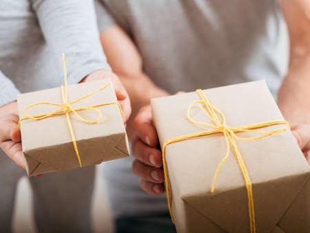 Foto de Special occasion celebration. Loving child and father holding paper wrapped gift boxes. - Imagen libre de derechos