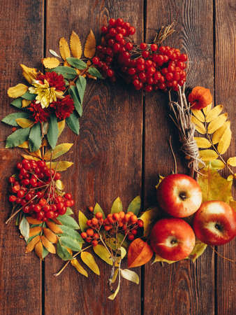 Photo pour Autumn wrench decor. Colorful fall plants, leaves arranged in round frame on brown wooden background. Copy space. - image libre de droit