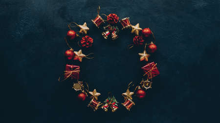Photo for New Year greeting card. Top view of Christmas wreath frame from ornaments on dark teal blue background. Copy space. - Royalty Free Image