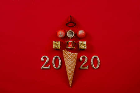 Photo pour Happy New Year 2020. Abstract Christmas tree arrangement in ice cream waffle cone and numbers on maroon background. Copy space. - image libre de droit