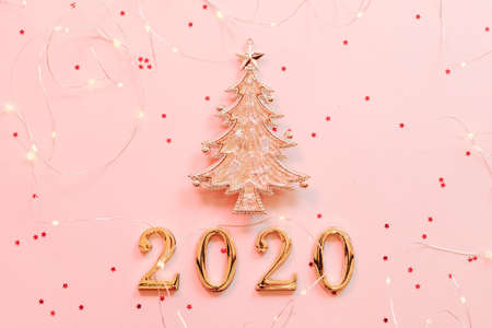 Photo for New Year 2020 greeting card. Flat lay of golden fir tree ornament and string lights on star pattern pink background. Copy space. - Royalty Free Image