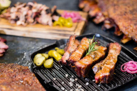 Foto de Grill restaurant. Closeup of smoked pork ribs on griddle pan. Pulled pork and ribs in background. - Imagen libre de derechos