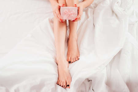 Photo pour Skin beauty care products. Cropped top view of woman with bare legs sitting on bed with pink gift box. - image libre de droit