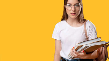 Smart student. High school. Woman in glasses holding notebooks. Isolated on orange copy space. Education courses. Knowledge and skills. Practical training