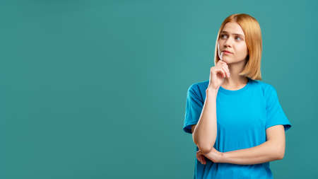 Photo pour Curious woman portrait. Special offer. Thoughtful doubtful blonde lady in blue t-shirt looking at copy space for brand text isolated on teal commercial background. Hard choice. - image libre de droit