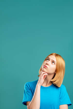 Photo pour Doubtful woman. Inspiration background. Portrait of curious blonde lady in blue t-shirt looking at copy space for text isolated on teal. Insight idea. Hard decision. - image libre de droit