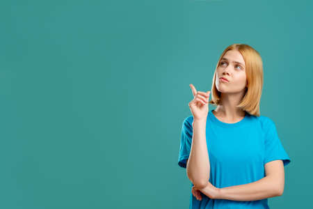 Photo pour Inspired woman portrait. Answer solution. Pensive blonde lady in blue t-shirt looking pointing at empty space for text isolated on teal promotional background. Insight idea. - image libre de droit