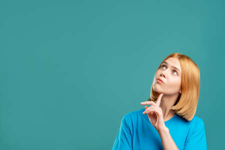 Photo pour Curious woman. Motivation background. Portrait of pensive blonde lady in blue t-shirt looking at empty space for information isolated on teal. Dream opportunity. - image libre de droit