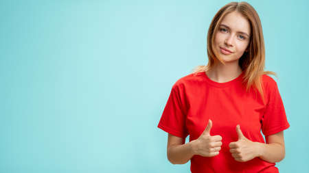 Photo pour Like gesture. Special offer. Portrait of satisfied confident woman in red t-shirt approving choice with thumbs up smiling isolated on blue copy space advertising background. Agreement acceptance. - image libre de droit