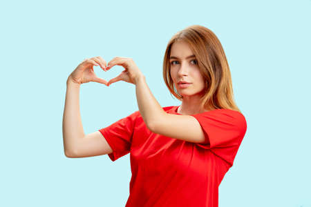 Photo pour Supportive woman portrait. Love sign. Grateful tender lady in red t-shirt showing heart gesture isolated on blue background. Compassion care. Insurance donation. - image libre de droit