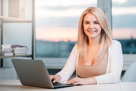 Foto de Business webinar. Virtual corporate meeting. Cheerful confident female CEO working with laptop at light cosy home office looking at camera. Video conference. COVID-19 quarantine. Social distancing. - Imagen libre de derechos