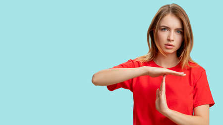 Photo pour Time up. Break gesture. Portrait of confident protesting woman in red t-shirt showing T sign with hands isolated on blue copy space background. Restriction rejection. Pause signal. - image libre de droit
