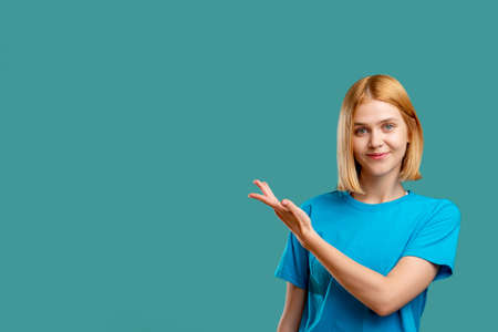 Photo pour Cheerful woman portrait. Commercial background. Positive blonde lady in blue t-shirt showing copy space looking at camera smiling isolated on teal. Special offer. - image libre de droit