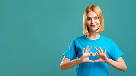 Photo pour Supportive woman. Love care. Cheerful lady in blue t-shirt showing heart gesture isolated on teal copy space advertising background. Romantic message. Admiration affection. - image libre de droit