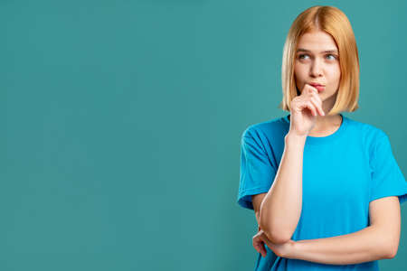 Photo pour Doubtful woman. Problem solution. Portrait of pensive blonde lady in blue t-shirt looking at copy space isolated on teal promotional background. Special offer. Motivation discovery. - image libre de droit