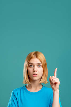 Photo pour Overwhelmed woman. Exciting opportunity. Portrait of inspired blonde lady in blue t-shirt pointing up at copy space isolated on teal commercial background. Surprising idea. - image libre de droit