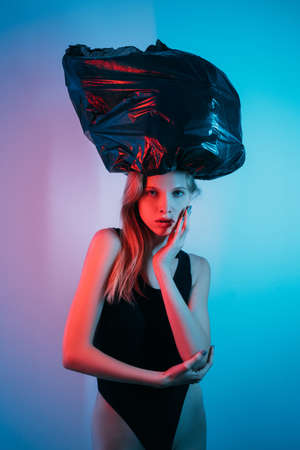 Photo for Art portrait. Heavy burden. Stress weight. Anxiety problem. Exhausted pensive woman suffering from pressure of black bag on head in red neon light isolated on blue pink color gradient background. - Royalty Free Image