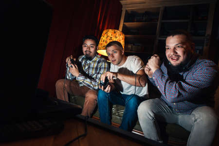 Three excited and concentrated young guys with joysticks play video game. Tensioned youth sit on couch in dark room with gamepad.