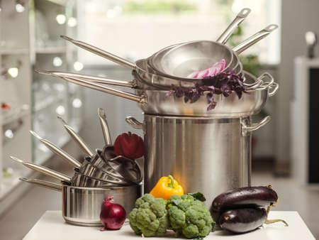 Photo pour Stack of professional kitchen pans. Restaurant cooking untensils. Healthy food and proper nutrition concept - image libre de droit