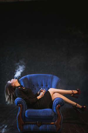 successful business woman smoking e-cigarette and having a drink. Unwinding and enjoying life after hard work.