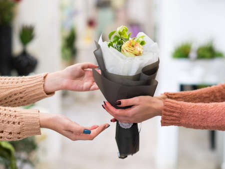 Photo pour Safe and quick flower bouquet delivery for someone you love. Women hands holding a creative arrangement of roses dahlia and berries - image libre de droit