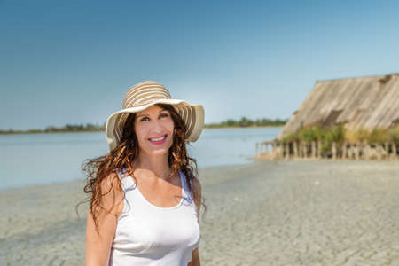 Attractive mature busty woman in very good shape with wide hat on a sun split beach with  straw hut