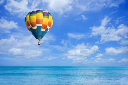 Photo pour Hot air balloon fly over the sea with clouds blue sky background - image libre de droit