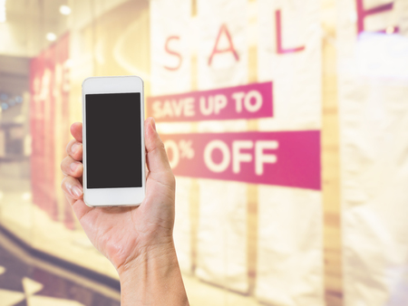 Hand holding mobile phone with blurred image of shopping mall