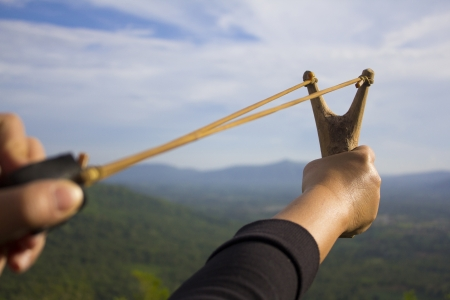 Photo pour Hand pulling sling shot preparing to shot the tree seed into the forest - image libre de droit