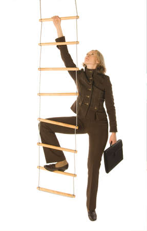 Photo for An isolated photo of a businesswoman climbing a rope-ladder - Royalty Free Image