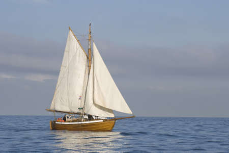 Tender with white sails in the calm sea