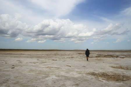 Man with backpack walking among waste landscape, salty lake Baskunckhak in summer
