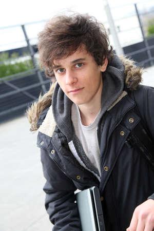 Portrait of teenage boy in front of school building