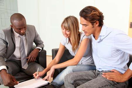 Photo pour Couple signing home-purchase contract - image libre de droit