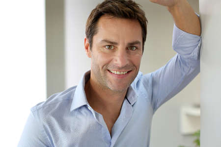 Portrait of handsome and happy guy leaning on wall