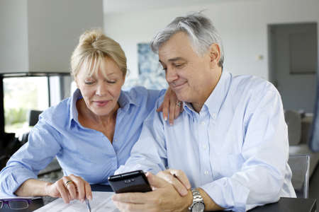 Senior couple calculting bills amount using smartphone